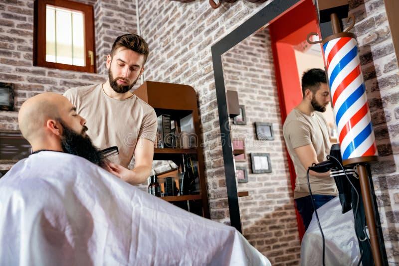 Cabeleireiro que faz o corte de cabelo da barba imagens de stock royalty free
