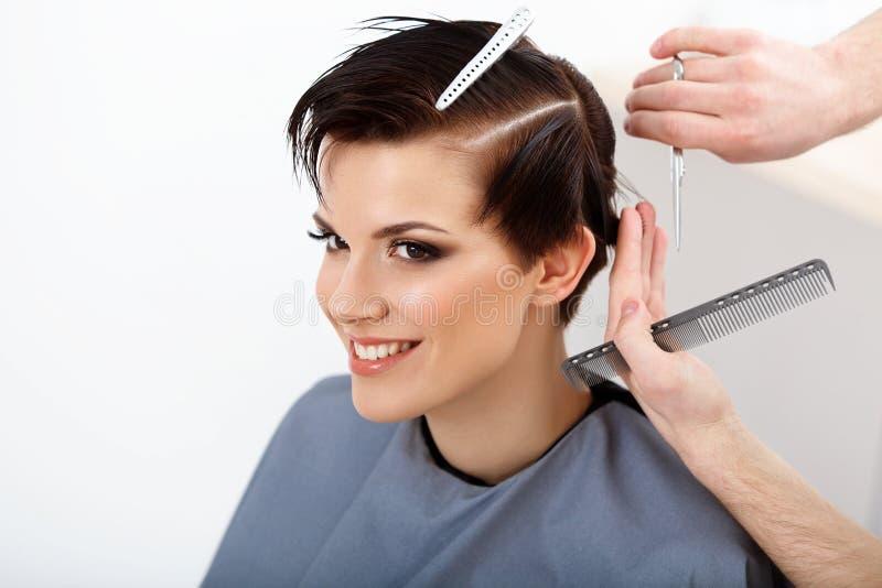 Cabeleireiro que faz o penteado Morena com cabelo curto cabelo Sa fotografia de stock royalty free