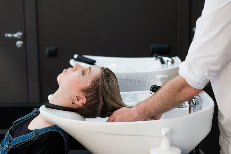 Cabeleireiro que lava o cabelo adolescente da menina no bar da beleza imagens de stock royalty free