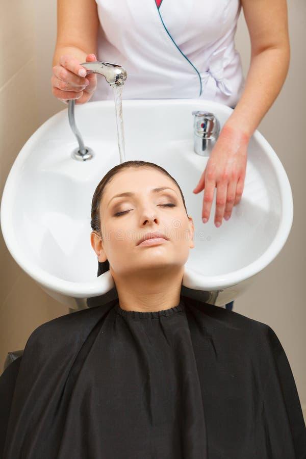Cabeleireiro que lava seu cabelo do cliente da mulher imagem de stock