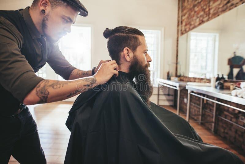 Cabeleireiro que põe o cabo do cabelo do corte sobre o cliente fotografia de stock