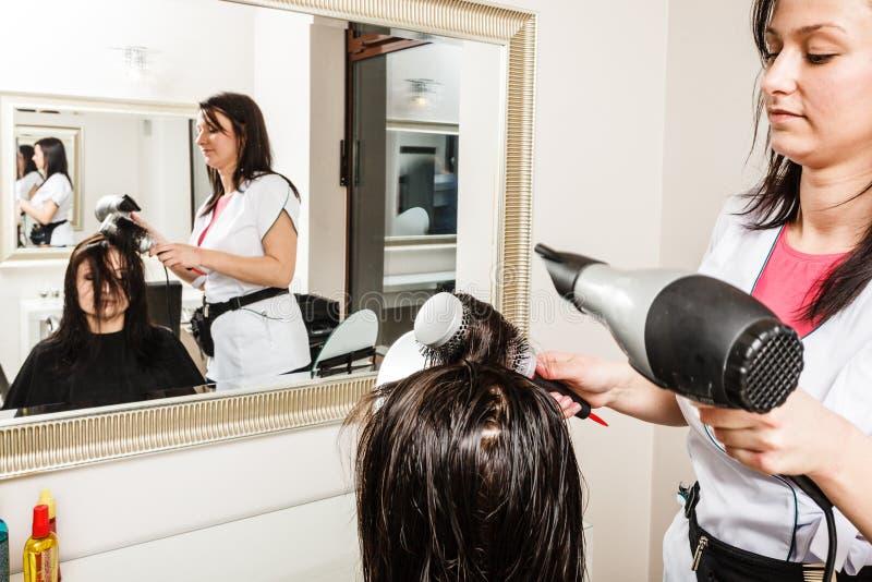 Cabeleireiro que seca o cabelo fêmea escuro usando o hairdryer profissional fotografia de stock royalty free