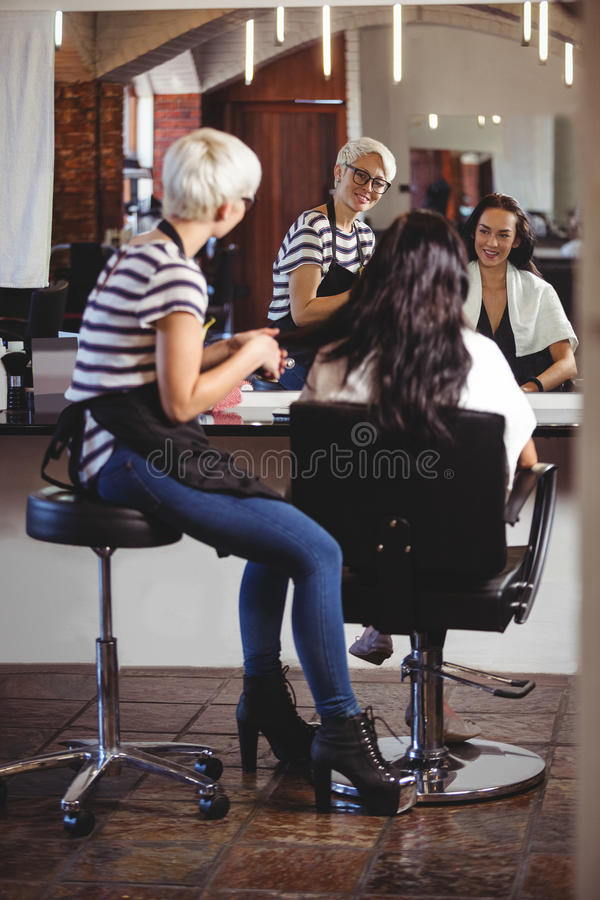Cabeleireiro que senta-se com o cliente no cabeleireiro imagem de stock royalty free