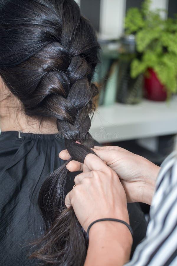 Cabeleireiro que trabalha com cabelo bonito da mulher cabeleireiro sa foto de stock