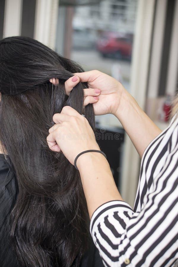 Cabeleireiro que trabalha com cabelo bonito da mulher cabeleireiro sa fotografia de stock