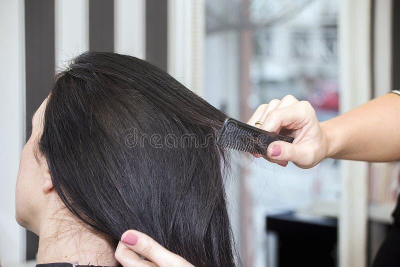 Cabeleireiro que trabalha com cabelo bonito da mulher cabeleireiro sa foto de stock royalty free