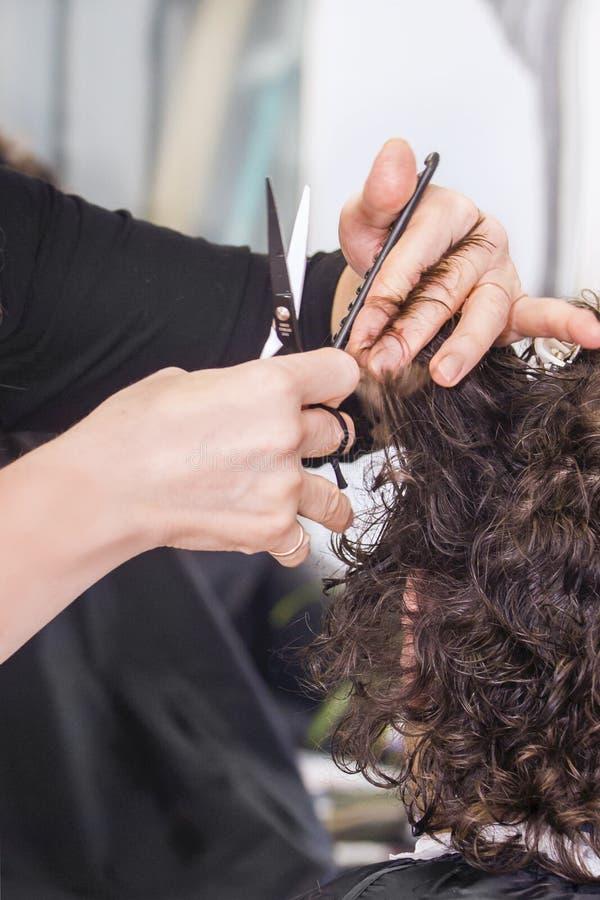 Cabeleireiro que trabalha com cabelo no salão de beleza do cabeleireiro imagem de stock royalty free
