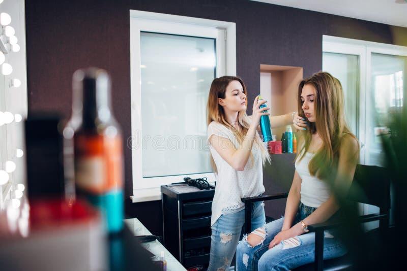 Cabeleireiro que usa a laca no cabelo da menina s que cria o penteado ocasional natural no salão de beleza do projeto do cabelo imagem de stock royalty free