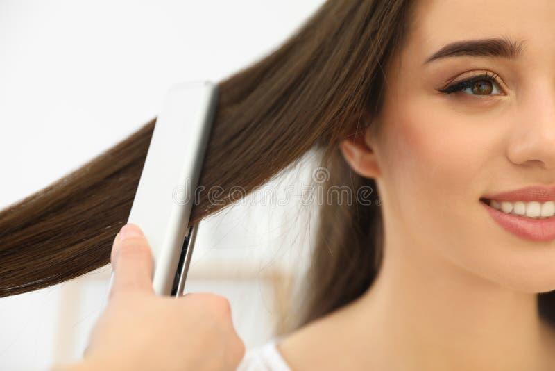 Cabeleireiro que usa o ferro liso moderno para denominar o cabelo do cliente no salão de beleza imagem de stock