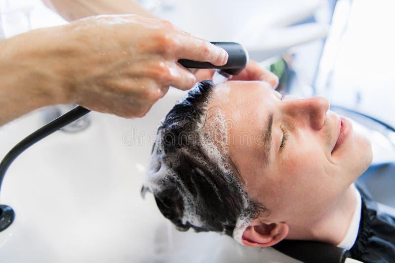 Cabeleireiro Washing Customer Hair do barbeiro - homem novo que relaxa no salão de beleza do cabeleireiro imagens de stock royalty free
