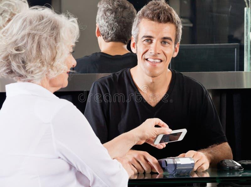 Cabeleireiro With Woman Paying através do telefone celular fotos de stock royalty free