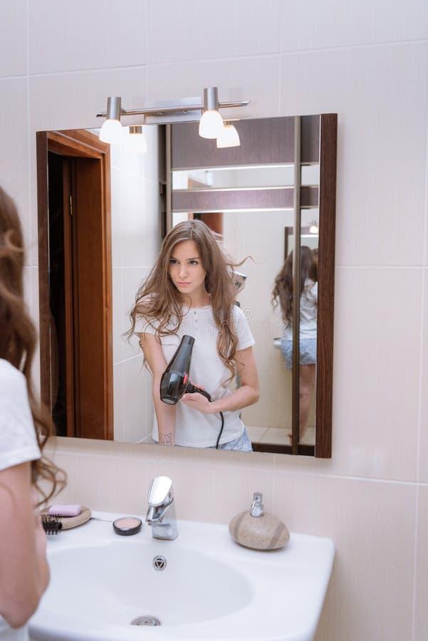 cabello seco de la mujer en cuarto de baño con el pelo imagenes de archivo
