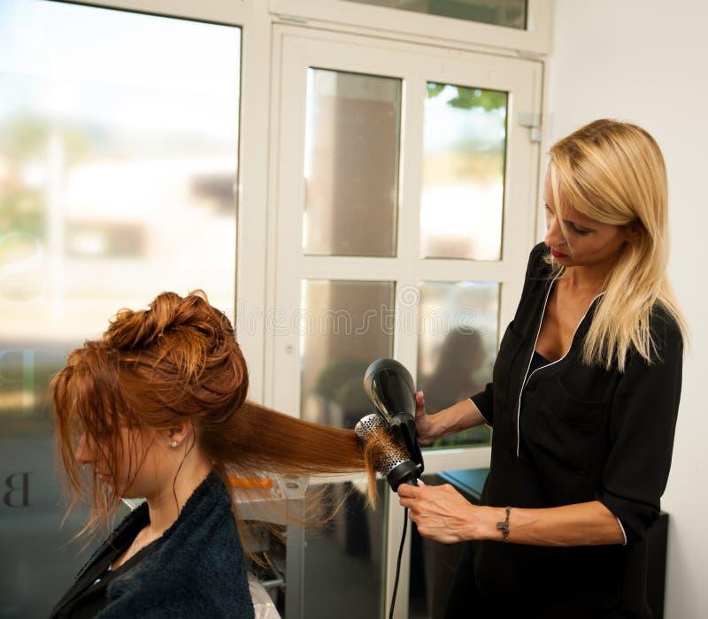 Cabello seco de un cliente femenino en el salón de belleza - hai del estilista foto de archivo