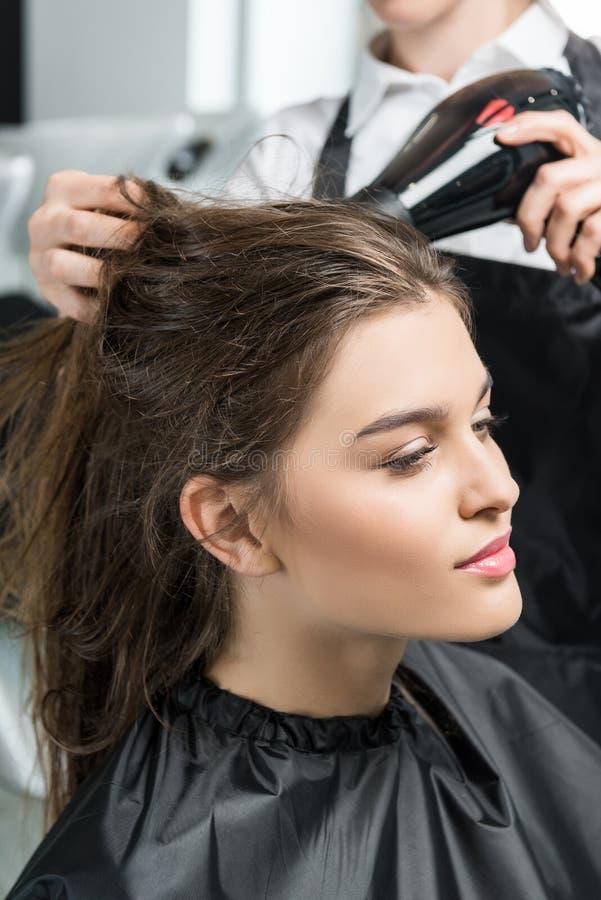 Cabello seco del peluquero de la mujer fotografía de archivo libre de regalías