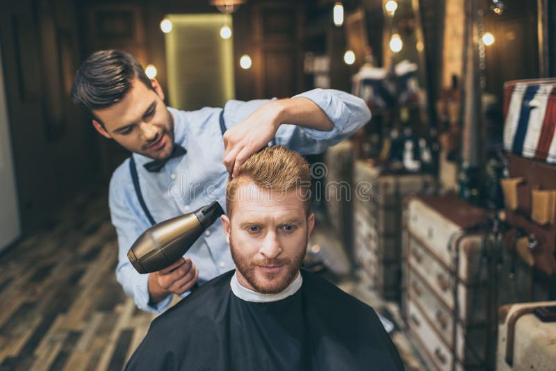 Cabello seco del peluquero joven del cliente con el secador de pelo imagen de archivo libre de regalías