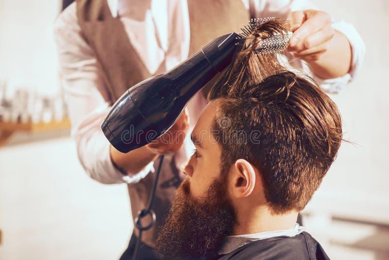 Cabello seco del peluquero profesional de su cliente fotografía de archivo