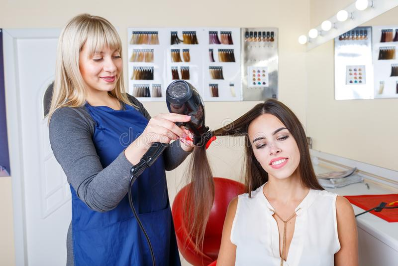 Cabello seco del peluquero si revistas de una lectura de la mujer en un fondo de la barbería Concepto de la profesión del peluque fotografía de archivo libre de regalías