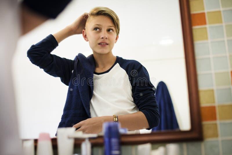 Cabelo ajustado do menino caucasiano novo com o espelho no banheiro foto de stock royalty free