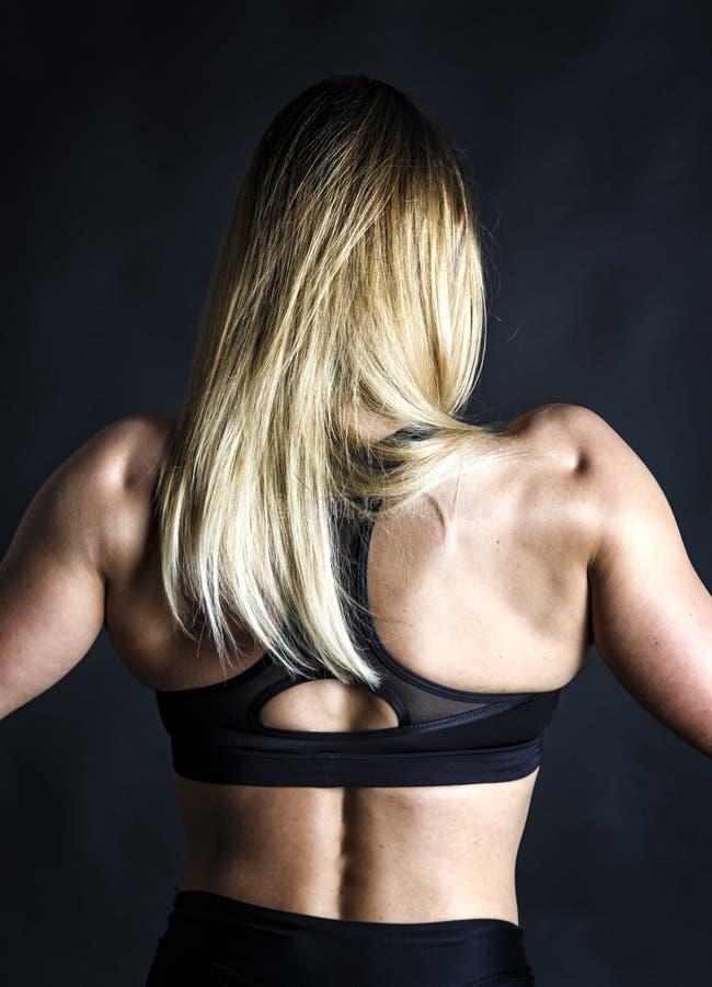 Cabelo branco longo da jovem mulher atlética que mostra os músculos da parte traseira e das mãos no fundo preto fotos de stock