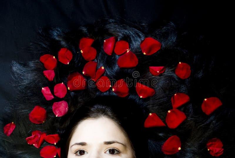Cabelo da mulher com pétalas cor-de-rosa imagens de stock royalty free