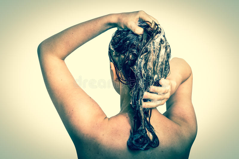 Cabelo de lavagem da mulher atrativa com champô no chuveiro foto de stock