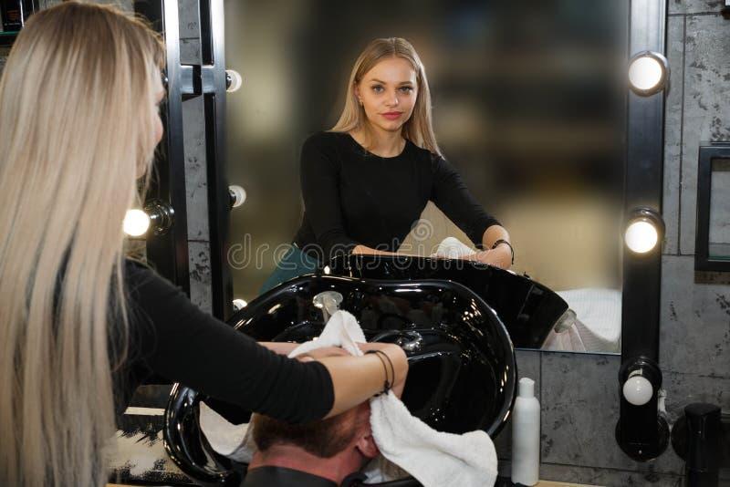 Cabelo de lavagem do ` s do cliente do barbeiro na barbearia imagem de stock royalty free