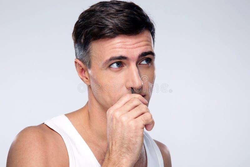 Cabelo de nariz pucking do homem com pinça fotos de stock royalty free