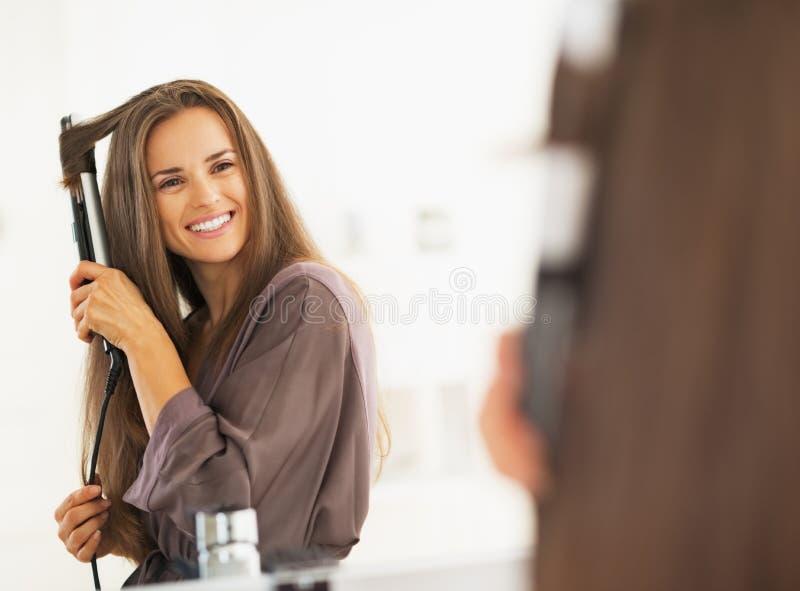 Cabelo de ondulação de sorriso da mulher com straightener fotografia de stock royalty free