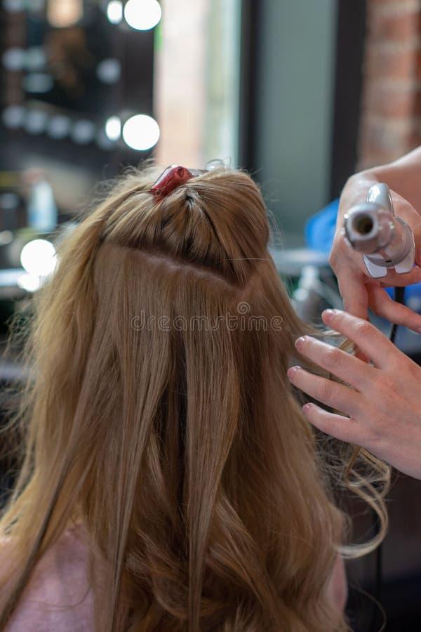 Cabelo de ondula??o do estilista para a jovem mulher Cuidado da menina sobre seu penteado Para fazer ondas imagens de stock royalty free