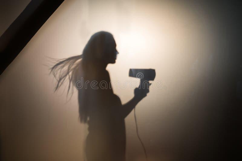 Cabelo de secagem da sombra da mulher imagens de stock royalty free