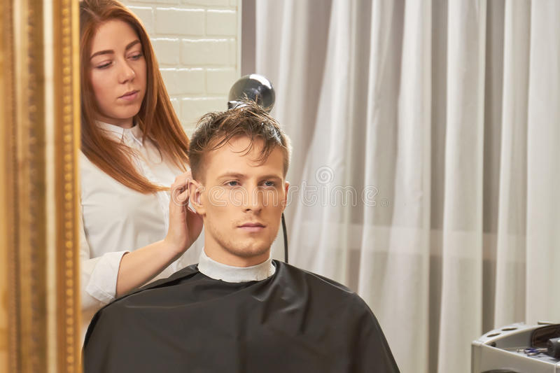 Cabelo de secagem do barbeiro fêmea imagens de stock royalty free