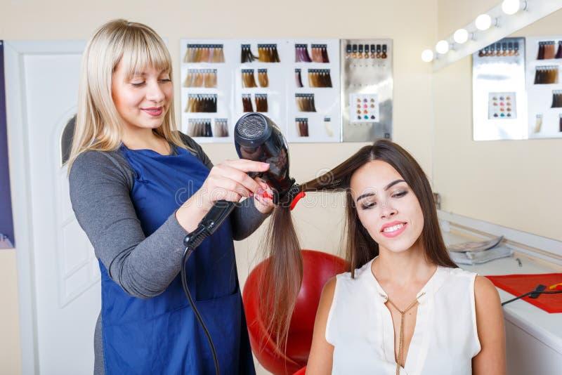 Cabelo de secagem do barbeiro se compartimentos de uma leitura da mulher em um fundo do barbeiro Conceito da profissão do barbeir fotografia de stock royalty free