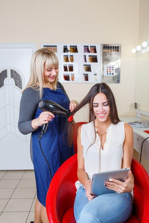 Cabelo de secagem do barbeiro se compartimentos de uma leitura da mulher em um fundo do barbeiro Conceito da profissão do barbeir fotos de stock royalty free