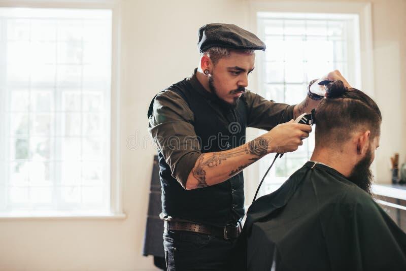 Cabelo do corte do barbeiro do cliente na barbearia imagem de stock
