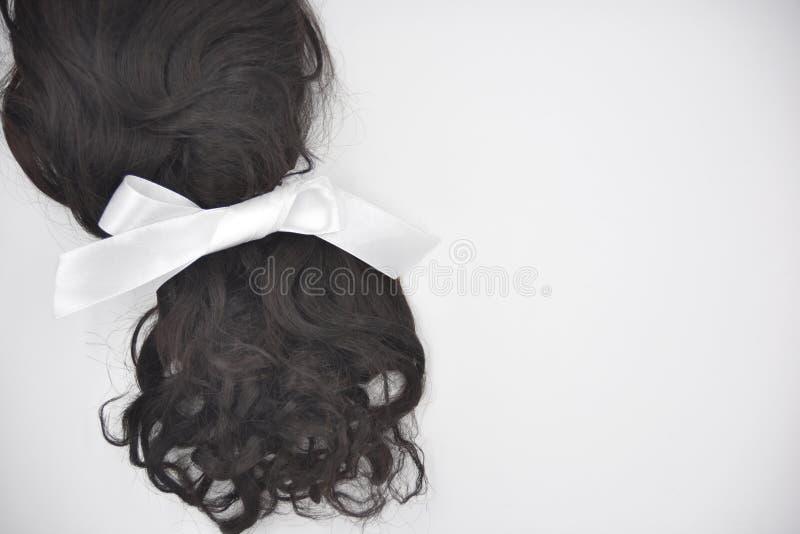 Cabelo encaracolado escuro com laço branco no fundo branco foto de stock royalty free