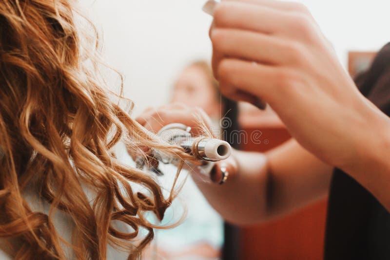 Cabelo encaracolado, mulher com cabelo ondulado louro longo que passa o, usando o ferro de ondulação, encrespador para ondas perf foto de stock