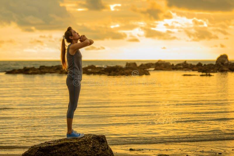 Cabelo longo, mulher asiática da boa forma que joga a ioga, exercício na rocha fotografia de stock
