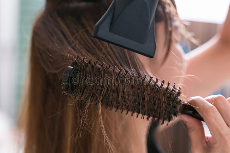 Cabelo louro de secagem com secador de cabelo e a escova redonda foto de stock royalty free