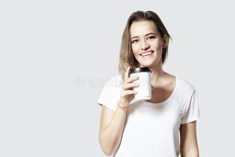 Cabelo louro de sorriso bonito da jovem mulher com a xícara de café do papel da eliminação, fundo branco isolado foto de stock royalty free