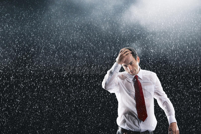 Cabelo molhado de Running Fingers Through do homem de negócios na chuva imagens de stock