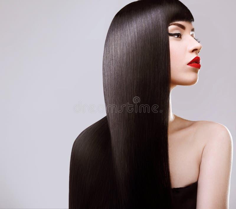 Cabelo. Mulher bonita com cabelo longo saudável. Bordos vermelhos foto de stock royalty free