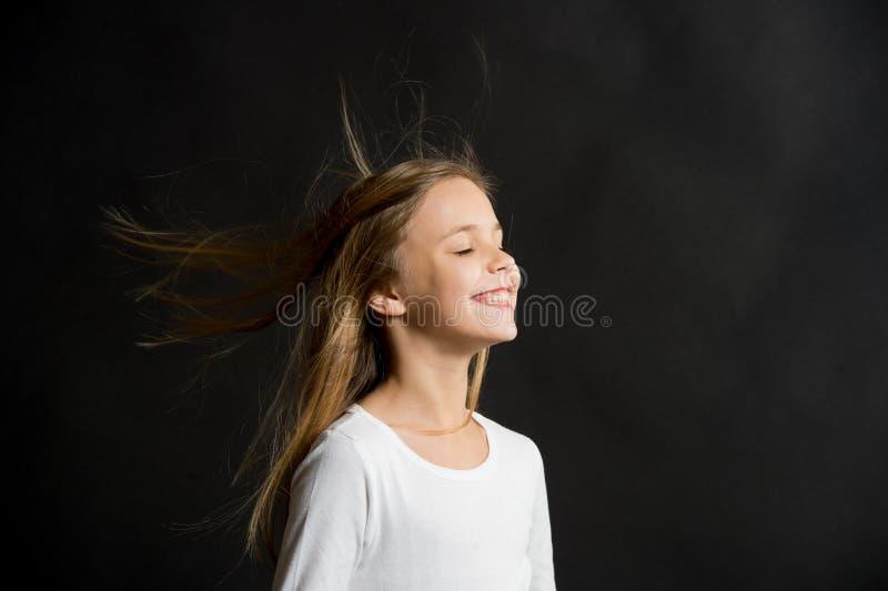 Cabelo natural Voo longo do cabelo da criança da menina no ar, fundo preto Criança com penteado saudável bonito natural fotos de stock