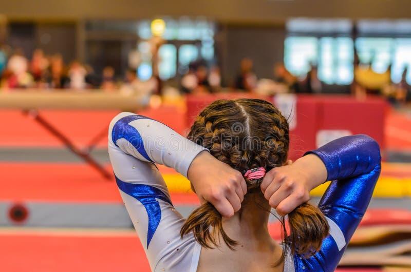Cabelo novo da fixação da menina da ginasta antes da aparência imagem de stock royalty free