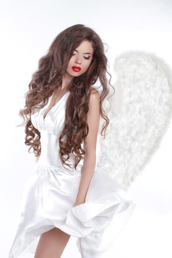Cabelo ondulado longo Angel Girl modelo no vestido de sopro com vitória branca fotografia de stock royalty free