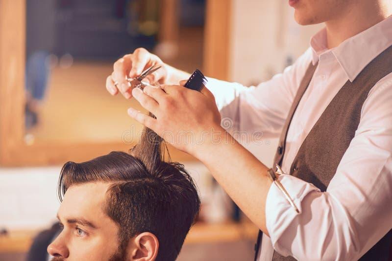 Cabelo profissional do corte do barbeiro de seu cliente imagem de stock