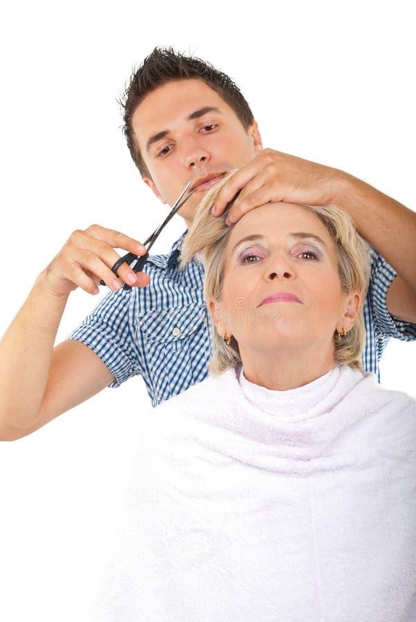 Cabelo sênior cortado cabeleireiro da mulher fotografia de stock royalty free
