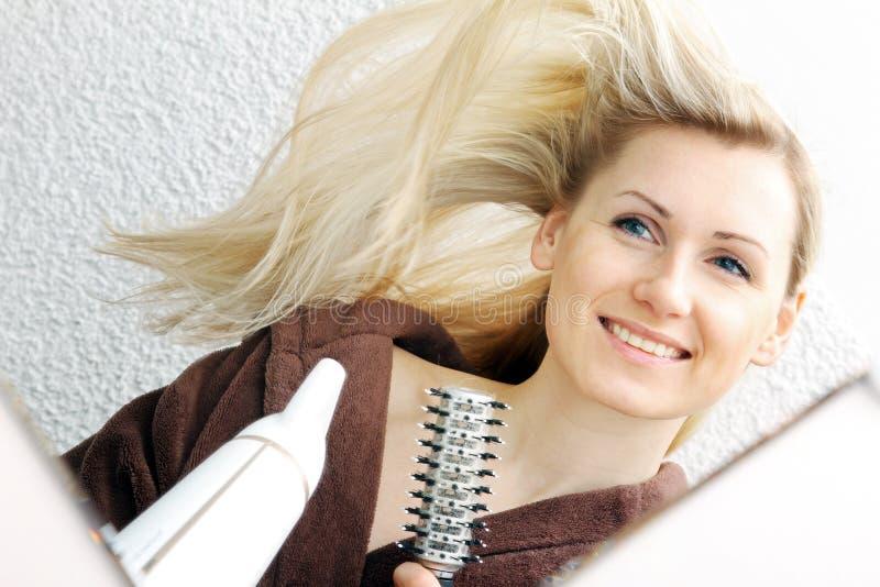 Cabelo secando da jovem mulher feliz no banheiro fotografia de stock royalty free