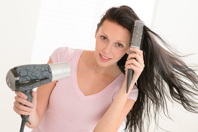 Cabelo secando da mulher usando-se em volta do hairbrush imagens de stock