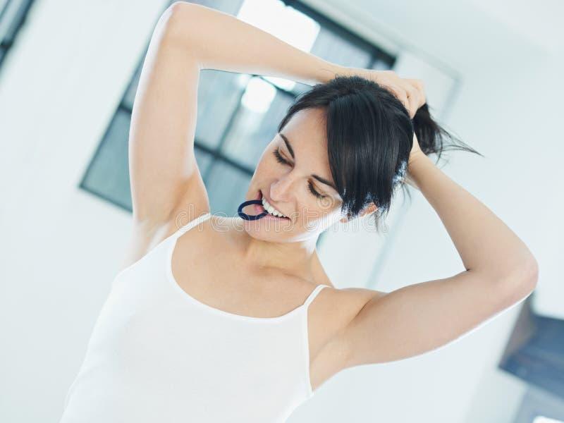 Cabelo tieing da mulher imagem de stock
