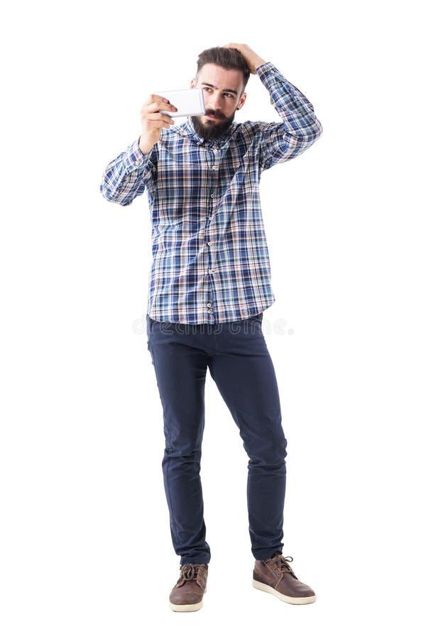 Cabelo tocante do homem farpado à moda macho seguro que olha a reflexão do telefone celular foto de stock